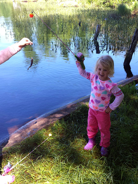Girl catching a small fish by the lake.